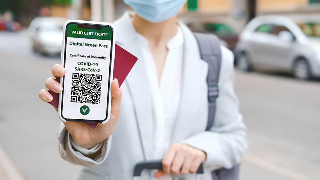 una viaggiatrice mostra lo schermo di uno smartphone con il green pass