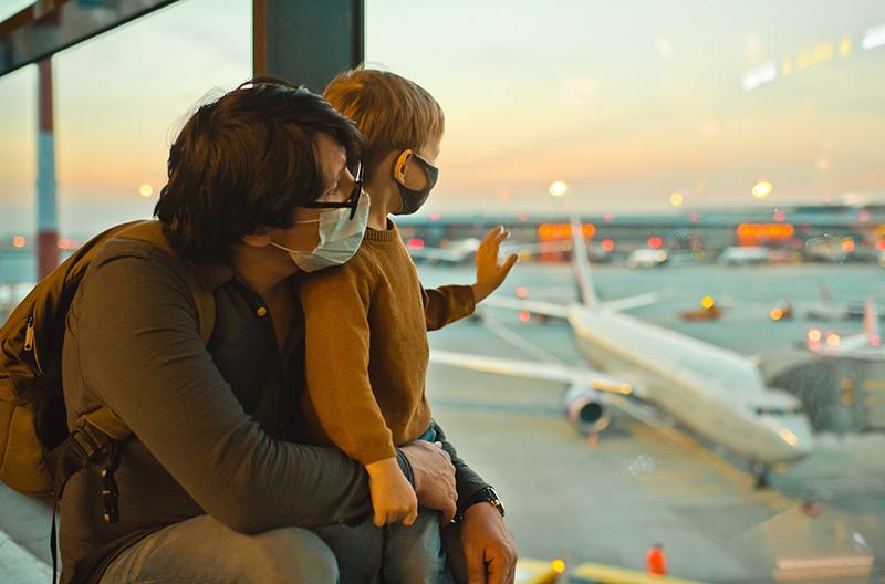 padre e figlio guardano aerei in partenza indossando la macherina